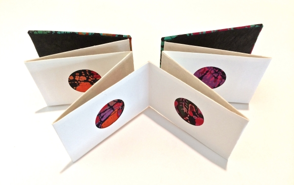 Accordion book with circle cut outs and batik fabric inserts