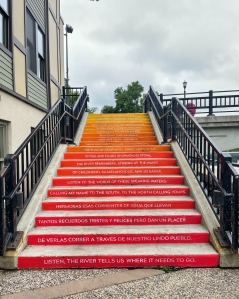 Rising stairs painted orange and yellow with a line of poetry stenciled on each step.